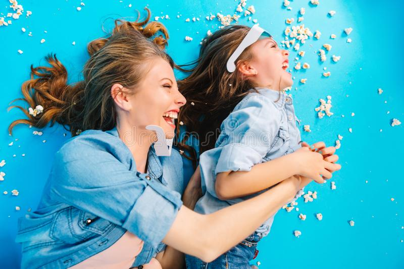Happy family moments of joyful mother tickling her little daughter on blue floor. Having fun in popcorn, crazy funny royalty free stock photos