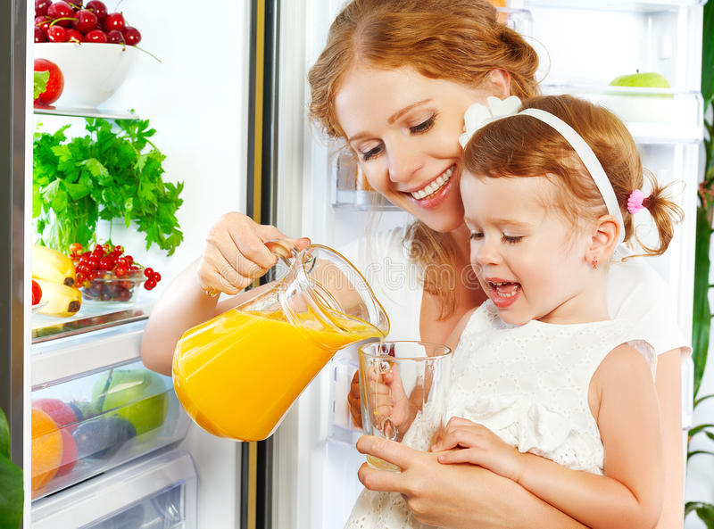 Happy family mother and baby daughter drinking orange juice in stock photography