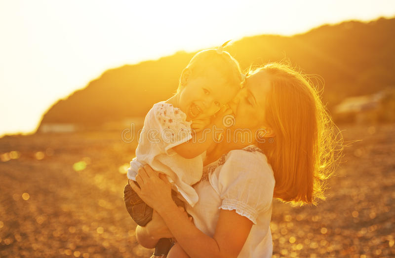 Happy family. Mother and baby girl daughter on beach at sunset royalty free stock photo