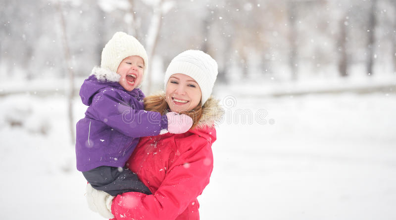 Happy family mother and baby girl daughter playing and laughing in winter snow royalty free stock photography