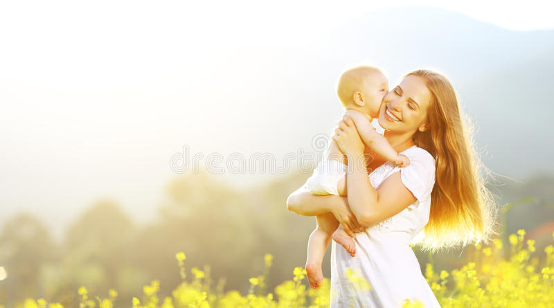 Happy family mother and baby hugging and kiss in summer on nature. Happy family mother and baby hugging and kiss in summer on the nature stock images