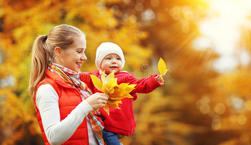 Happy family mother and baby laugh in nature autumn. Happy family mother and baby laugh with leaves in nature autumn royalty free stock images