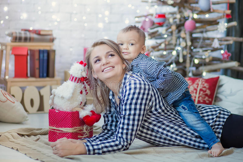 Happy family mother and baby little son playing home on Christmas holidays. New Year`s holidays. Toddler with mom in the stock photo