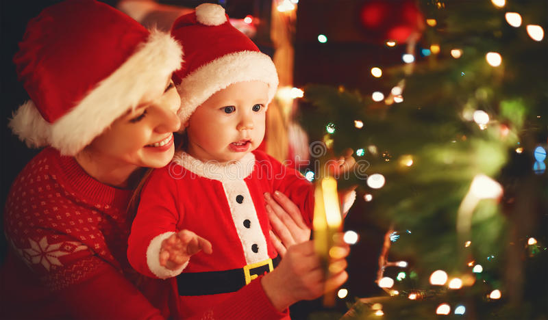Happy family mother and baby near Christmas tree in holiday nigh. Happy family mother and baby near Christmas tree in the holiday night stock photo