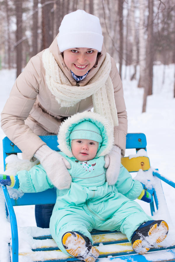 Happy family mother and baby in park in winter stock photos