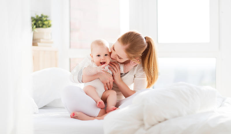 Happy family mother with baby playing and hug in bed royalty free stock photos