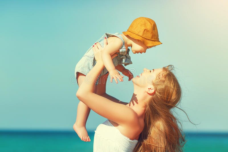 Happy family mother with baby son walks by ocean on beach in sum. Happy family mother with baby son walks by ocean on the beach in summer stock image