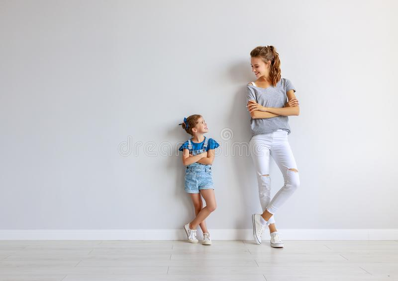 Happy family mother big sister and child daughter near an empty wall. Happy family mother big sister and child daughter near an empty brick wall stock photos