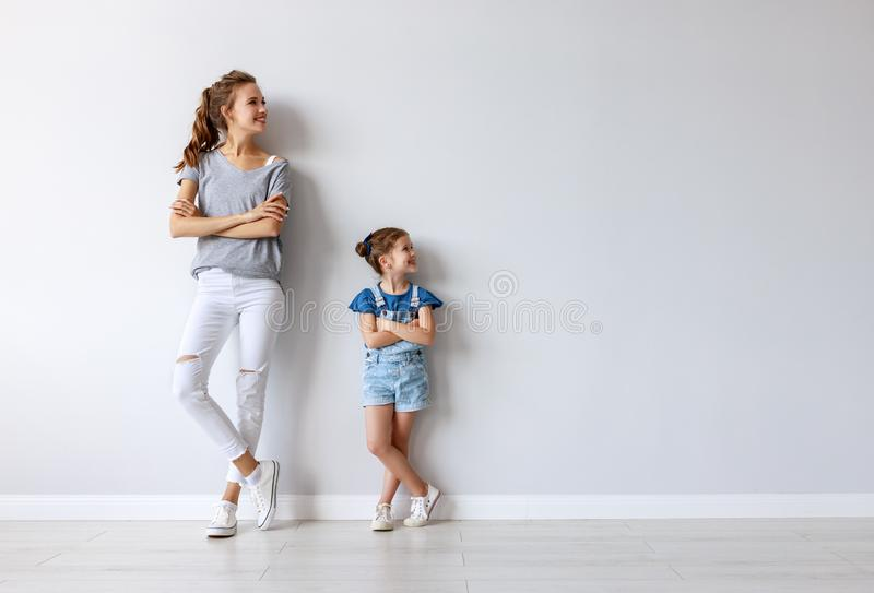 Happy family mother big sister and child daughter near an empty wall royalty free stock photos