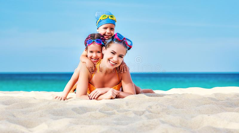Happy family mother and chidren in masks on beach in summer. Happy family mother and chidren in masks for swimming on the beach in summer royalty free stock photos