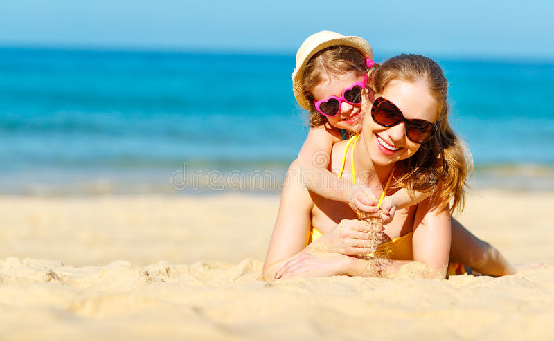 Happy family mother and child daughter on beach in summer stock photos