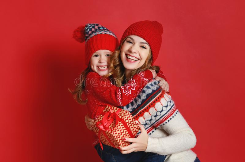 Happy family mother and child daughter with christmas gifts on r. Happy family mother and child daughter with christmas gifts and hats on red background stock images