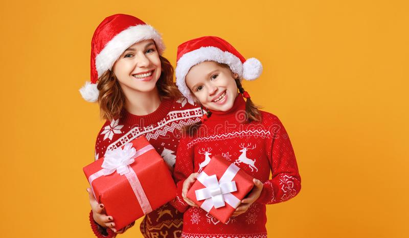 Happy family mother and child daughter  with christmas gifts on yellow background stock photo