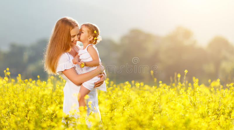 Happy family mother and child daughter embrace on nature in sum. Happy family mother and child daughter embrace on yellow flowers on nature in summer stock image