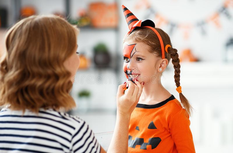 Happy family  getting ready for halloween make make-up. Happy family mother and child daughter getting ready for halloween make make-up royalty free stock image