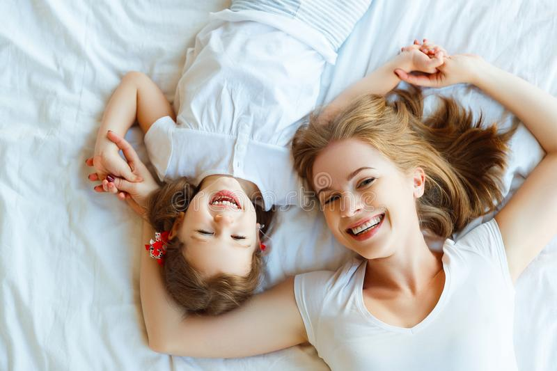 Happy family mother and child daughter laugh in bed stock photography