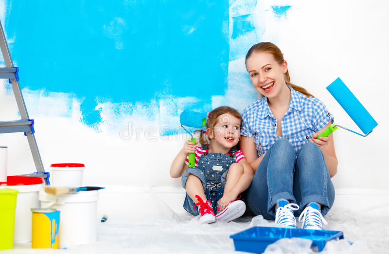 Happy family mother and child daughter making repairs, paint wal royalty free stock images