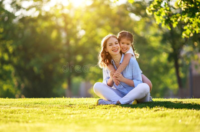 Happy family mother and child daughter in nature   in summer. Happy family mother and child daughter in nature Park in summer on green grass royalty free stock image