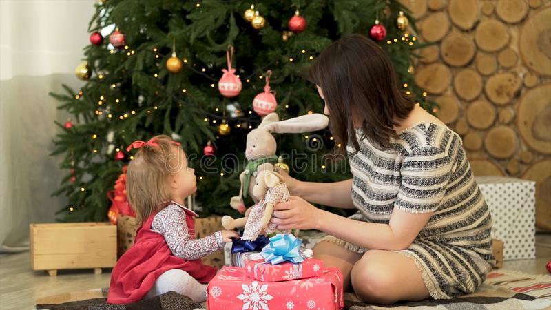 Happy family, mother and child daughter near decorated Christmas tree with gifts playing with toys. Beautiful, brunette royalty free stock photos