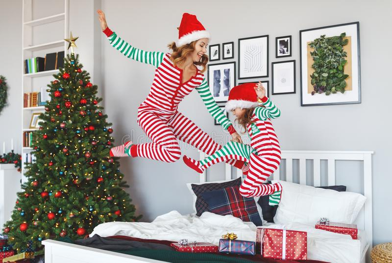 Happy family mother and child daughter in pajamas jumping in bed on on christmas morning. A happy family mother and child daughter in pajamas jumping in bed on royalty free stock images