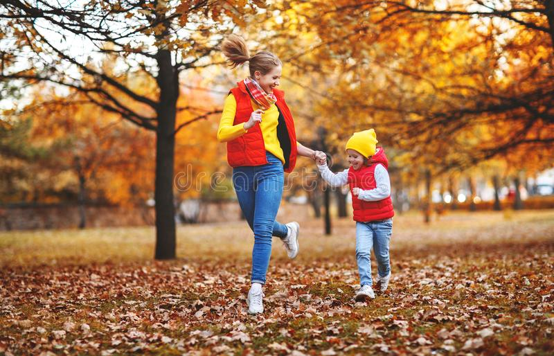 Happy family mother and child daughter on autumn walk. Happy family mother and child daughter playing and laughing on autumn walk stock photo