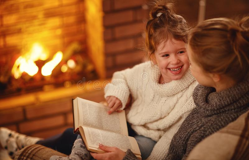 Happy family mother and child daughter read book on winter evening near fireplace. Happy family mother and child daughter read a book on winter autumn evening royalty free stock image