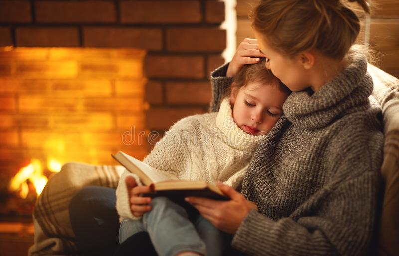Happy family mother and child daughter read book on winter evening near fireplace. Happy family mother and child daughter read a book on winter autumn evening stock image