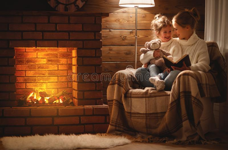 happy family mother and child daughter read book on winter evening near fireplace royalty free stock image