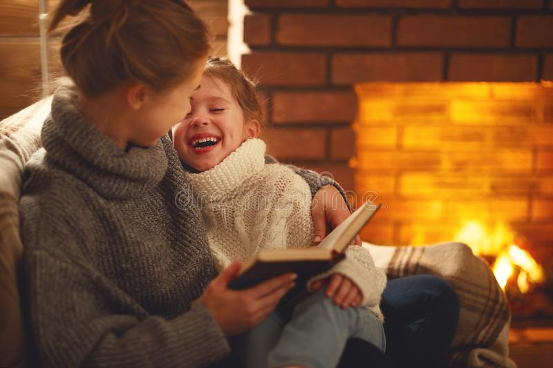 Happy family mother and child daughter read book on winter evening near fireplace. Happy family mother and child daughter read a book on winter autumn evening royalty free stock photo
