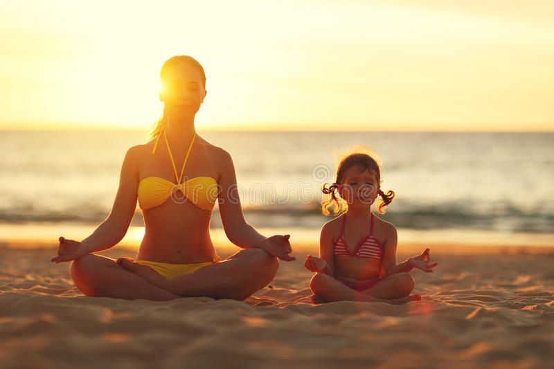 Happy family mother and child doing yoga, meditate in lotus position on beach . stock images