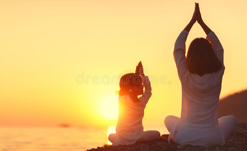 Happy family mother and child doing yoga, meditate in lotus position on beach. Happy family mother and child daughter doing yoga, meditate in lotus position on royalty free stock photo