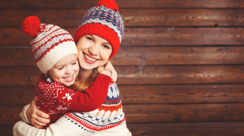 Happy family mother and child girl with christmas hat hugs at wooden. Background stock photo