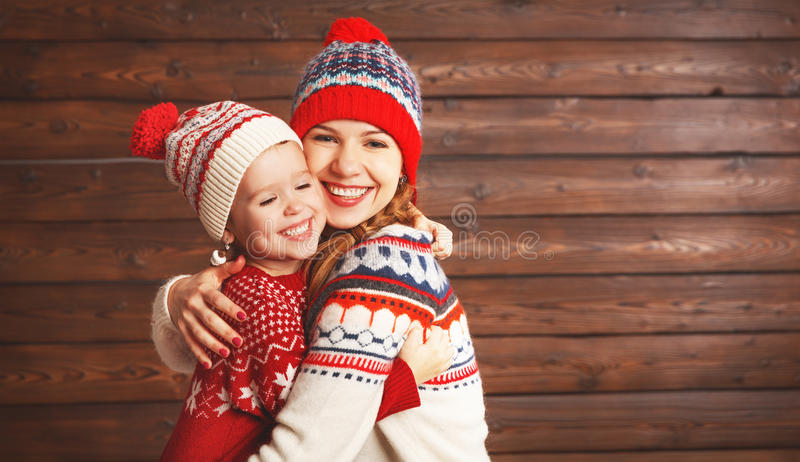 Happy family mother and child girl with christmas hat hugs at wooden. Background royalty free stock photo