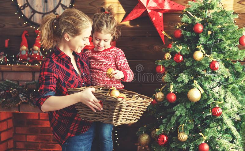 Happy family mother and child girl decorated Christmas tree royalty free stock image