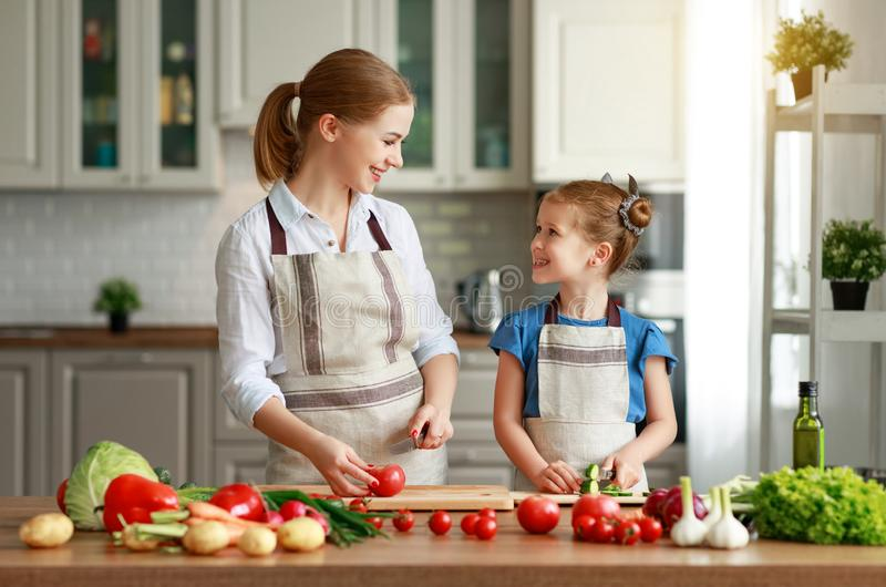 Happy family mother with child girl preparing vegetable salad. Happy family mother with child girl   preparing vegetable salad at home stock photos