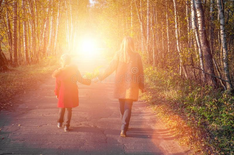 Happy family mother and child hold hands on an autumn walk on a sunny day royalty free stock images