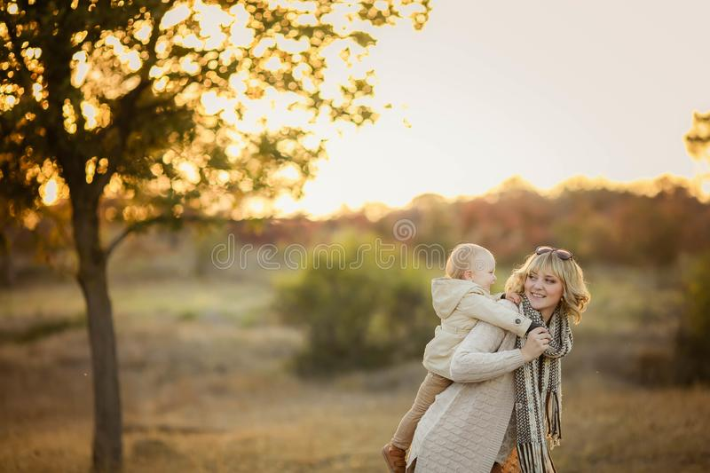 Happy family: mother and child little daughter play cuddling on autumn walk in nature outdoors stock image