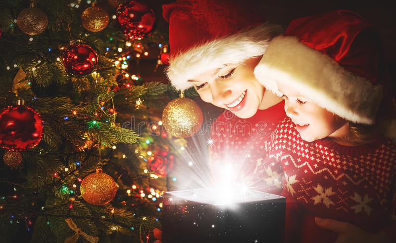 Happy family mother and child with magical Christmas gift. Happy family mother and child daughter with magical gift from the Christmas tree stock photo