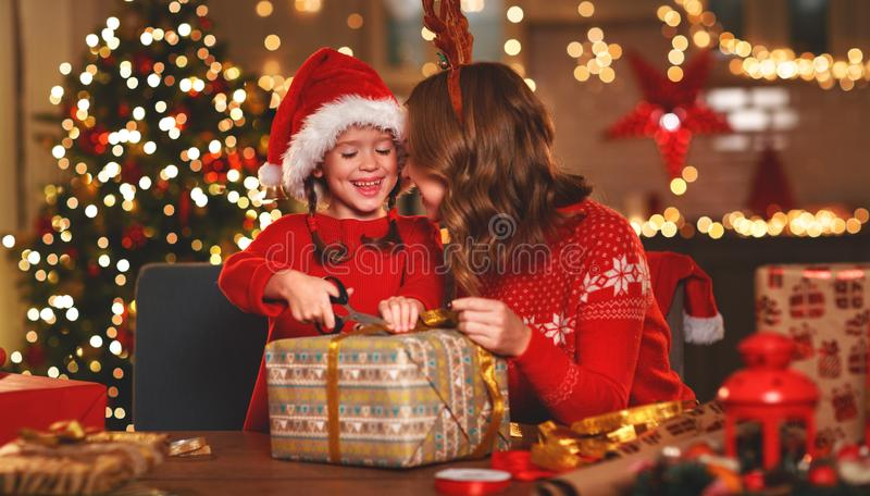 Happy family mother and child pack Christmas gifts. A happy family mother and child pack Christmas gifts royalty free stock photo