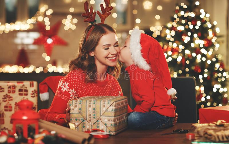Happy family mother and child pack Christmas gifts. A happy family mother and child pack Christmas gifts stock images