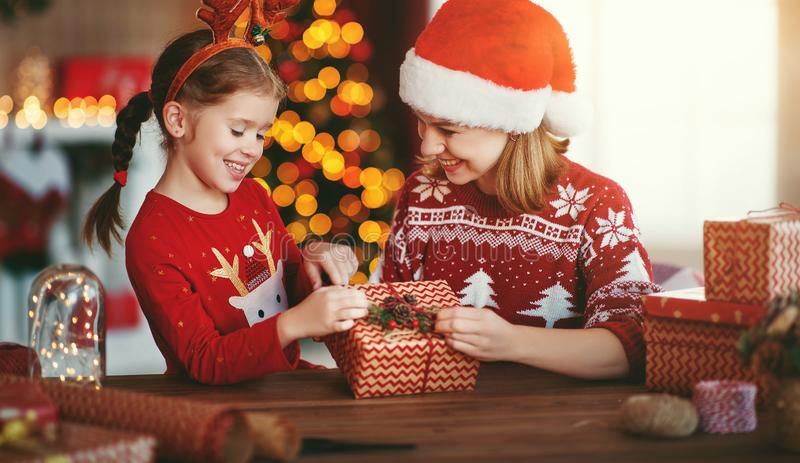Happy family mother and child pack Christmas gifts at home near Christmas tree royalty free stock photography