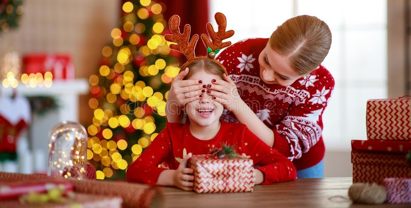Happy family mother and child pack Christmas gifts at home near Christmas tree stock images