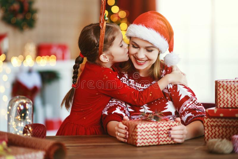Happy family mother and child pack Christmas gifts at home near Christmas tree royalty free stock photo