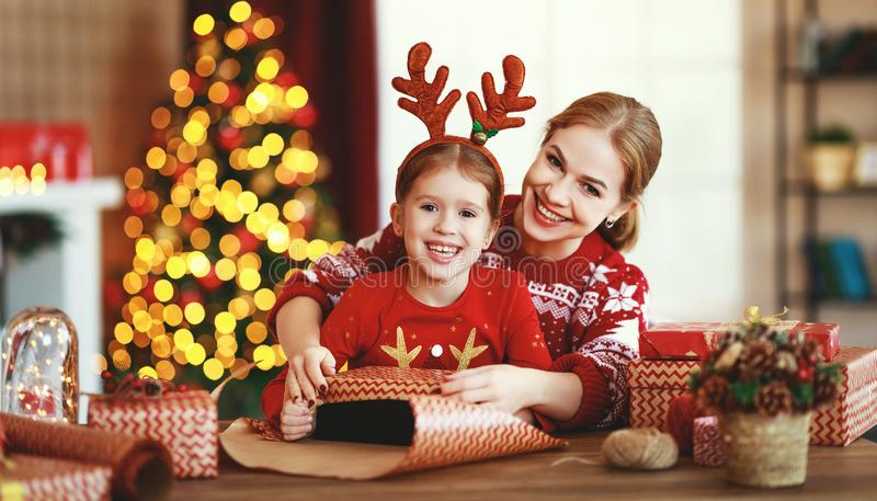 Happy family mother and child pack Christmas gifts at home near Christmas tree stock photography