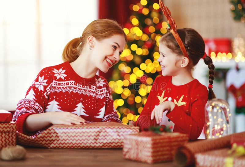 Happy family mother and child pack Christmas gifts at home near Christmas tree stock photo