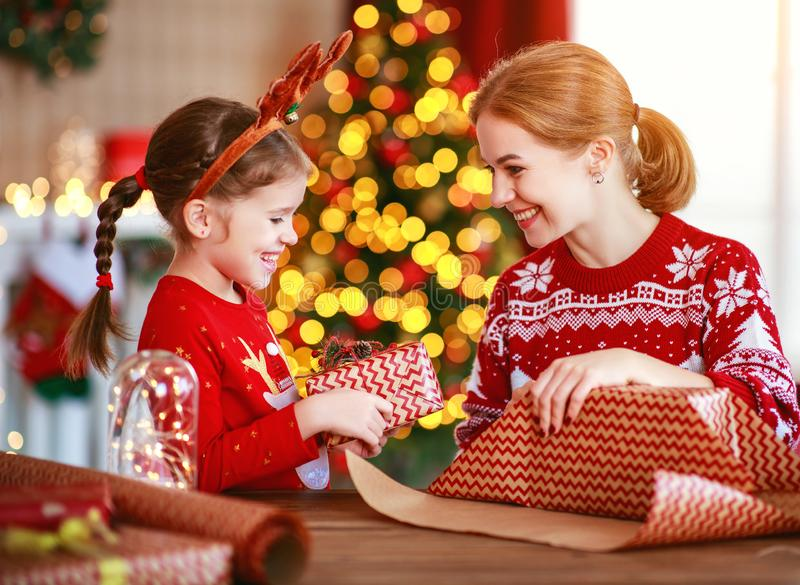 Happy family mother and child pack Christmas gifts at home near Christmas tree royalty free stock image
