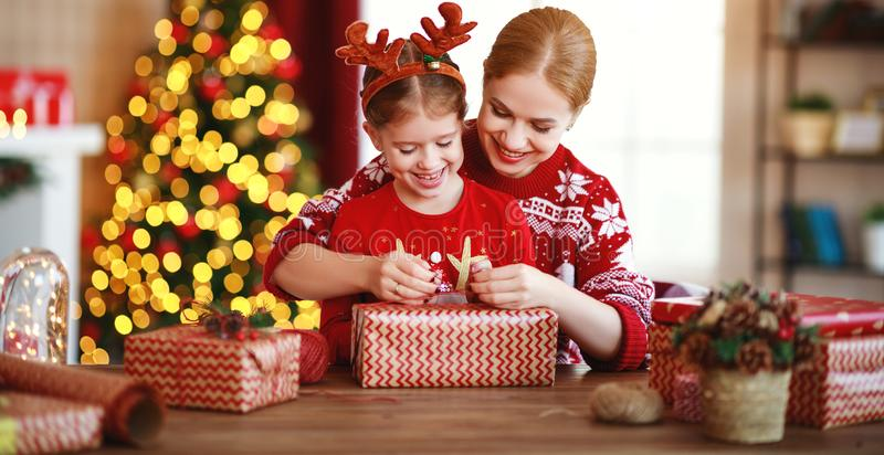 Happy family mother and child pack Christmas gifts at home near Christmas tree royalty free stock photos