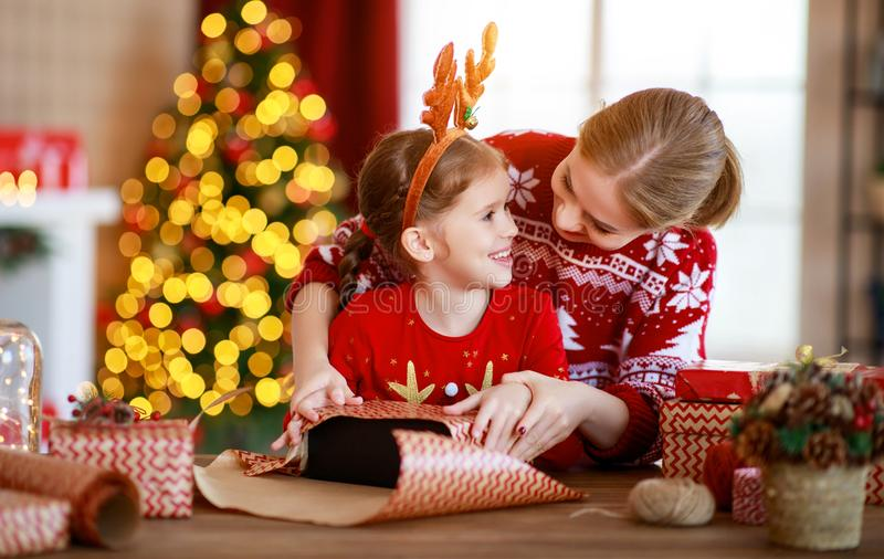 Happy family mother and child pack Christmas gifts at home near Christmas tree stock image