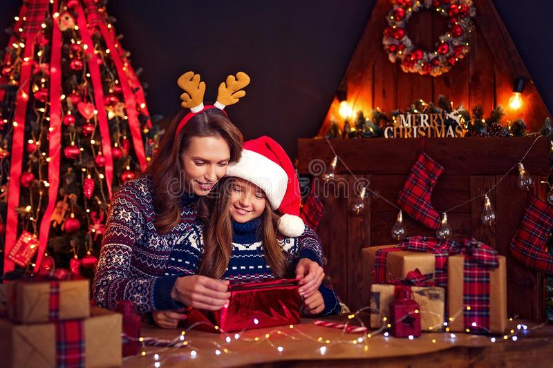 A happy family mother and child pack Christmas gifts stock images