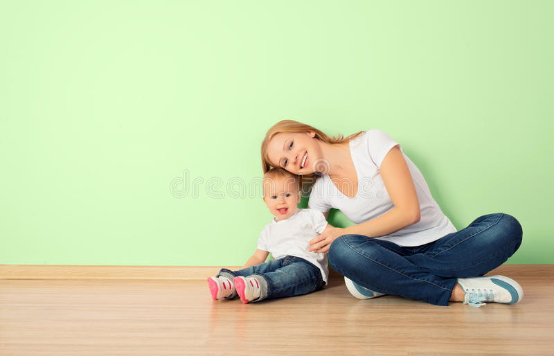 happy family of mother and child sitting on the floor in an empty wall royalty free stock photos